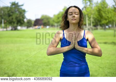 Woman Practicing Yoga Performing Yoga-asanas Outdoors. Young Slim Fitness Woman In Bodysuit Relaxing