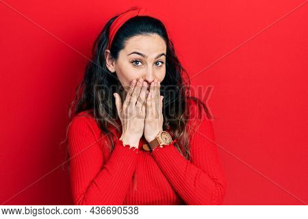 Young hispanic woman wearing casual clothes laughing and embarrassed giggle covering mouth with hands, gossip and scandal concept