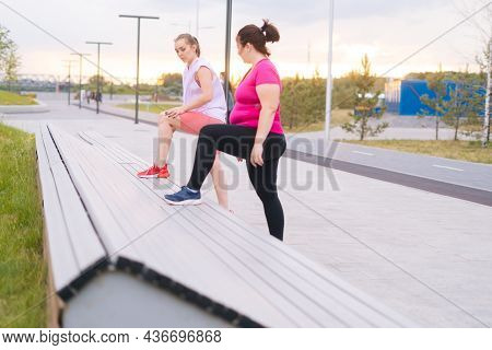 Overweight Young Woman Doing Single Leg Squats Using Bench With Personal Trainer Outdoor In Summer M