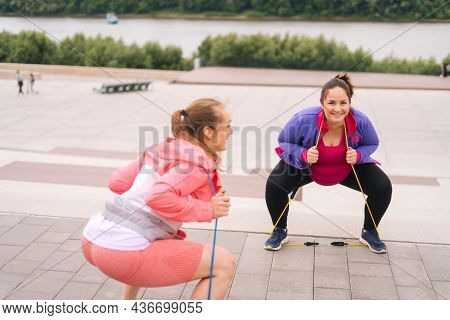 Wide Shot Of Overweight Young Woman Doing Squats Exercises Using Fitness Tape For Weight Loss With P
