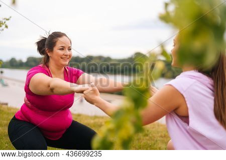 Medium Shot Of Professional Fitness Female Trainer Giving Personal Training To Overweight Young Woma