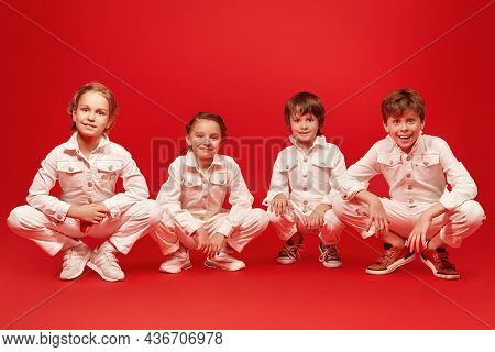 Cheerful kids in white overalls cheerfully pose together sitting in a row. Festive red background. Kid's fashion. Happy childhood.