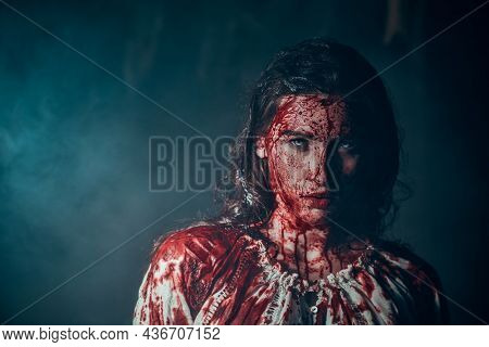 Spooky portrait of a beautiful innocent girl drenched in blood standing in a dark gloomy room. Horror, thriller. Halloween. Vampires.