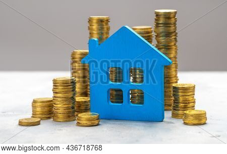 Expensive Real Estate. Blue House And Stacks Of Gold Coins On A Gray Background