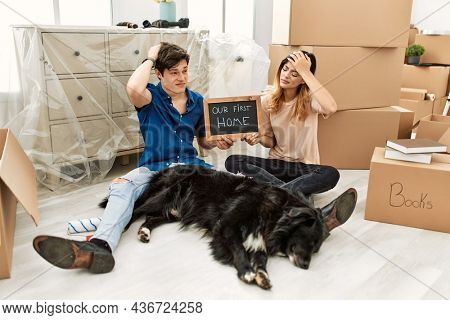 Young caucasian couple with dog holding our first home blackboard at new house confuse and wondering about question. uncertain with doubt, thinking with hand on head. pensive concept.