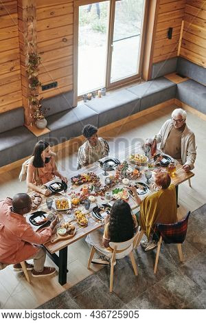 High angle view of family talking to each other during dinner at dining table at home
