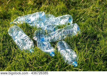 Empty Bottles On Grass Close-up. Plastic Trash On Green Moss Background. The Concept Of Environmenta