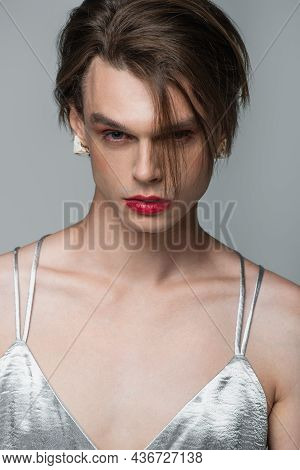 Young Transgender Man With Makeup And Earring Looking At Camera Isolated On Grey