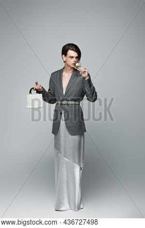 Full Length Of Transgender Man In Slip Dress And Blazer Drinking Wine While Holding Purse On Gray