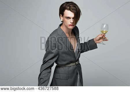 Young Transgender Man In Blazer Biting Lip While Holding Glass Of Wine Isolated On Grey