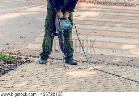 Worker With Pneumatic Hammer Drill Equipment. Road Repairing Works With Jackhammer