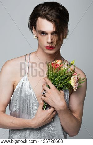 Young Transgender Man In Slip Dress Holding Flowers Isolated On Gray