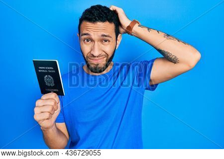 Hispanic man with beard holding italy passport confuse and wondering about question. uncertain with doubt, thinking with hand on head. pensive concept.