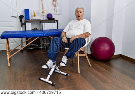 Senior caucasian man at physiotherapy clinic using pedal exerciser afraid and shocked with surprise expression, fear and excited face.