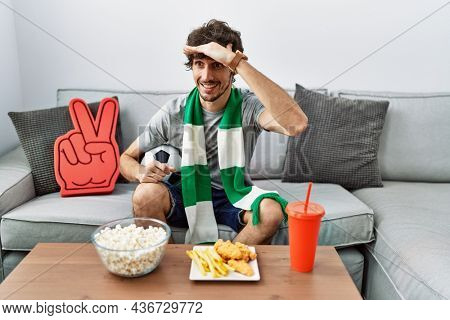 Young hispanic man football hooligan cheering game at home very happy and smiling looking far away with hand over head. searching concept.