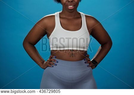 Young smiling plus size sportswoman in activewear keeping her hands on hips