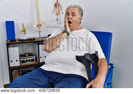 Senior caucasian man at physiotherapy clinic holding crutches afraid and shocked, surprise and amazed expression with hands on face