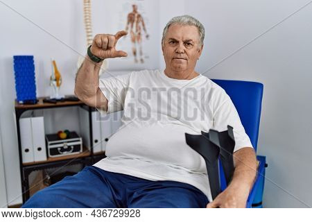 Senior caucasian man at physiotherapy clinic holding crutches smiling and confident gesturing with hand doing small size sign with fingers looking and the camera. measure concept.