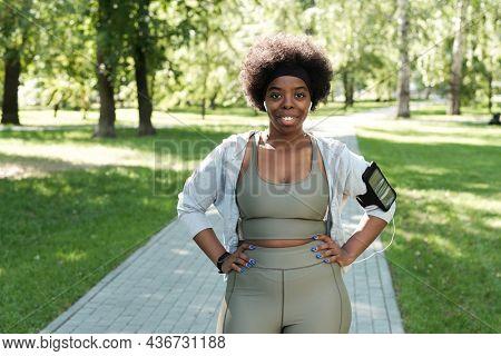 Happy plus size sportswoman standing in park while having break between jogging