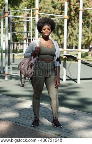 Young happy African sportswoman with handbag standing on sportsground before training