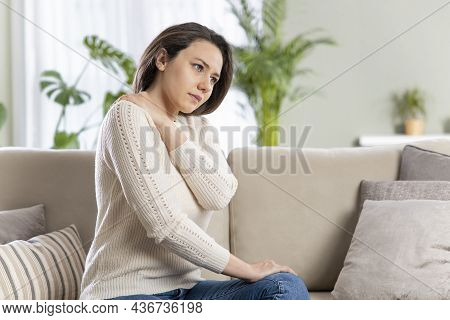 Young Woman Is Sitting At Home On Her Sofa And Touching The Back Of Her Neck While Suffering From Ne
