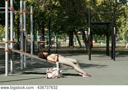 Young restful sportswoman enjoying music in earphones while relaxing on sports facilities on sportsground