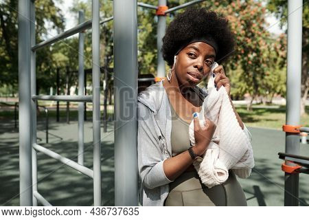 Young sportswoman with soft white towel having rest after training on sportsground