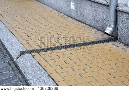 Facade Of Building With Granite Stone Cladding With Storm Pipe Into Drainage Canal With Iron Grating