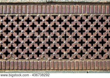 Retro Drainage Grate With Cross-hole Pattern Corroded Iron Cover Of Storm System Close-up.