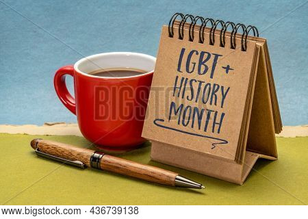 LGBT History Month - handwriting in a small desktop calendar with a cup of coffee against abstract paper landscape, reminder of cultural and heritage event