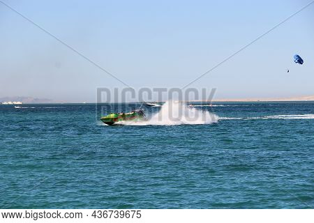 Hurghada / Egypt. 30 July 2018: Fast Boat Making Great Splashes On Sea Water And Rolling Tourists On