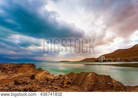 Low winter clouds are reflected in the green water. The smooth surface of the salty sea reflects the sky and clouds. Israel, legendary Dead Sea.