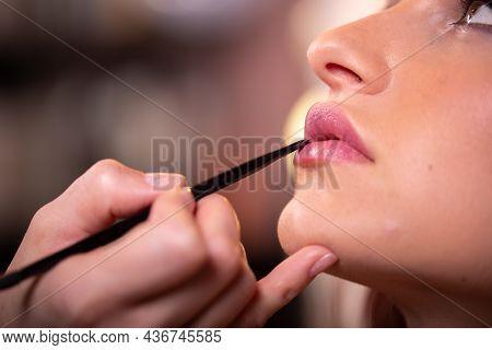 Makeup Artist Applies Pink Gloss Lipstick . Beautiful Woman Face. Hand Of Make-up Master, Painting L