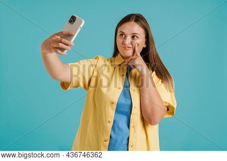 Young white woman grimacing while taking selfie photo on cellphone isolated over blue background