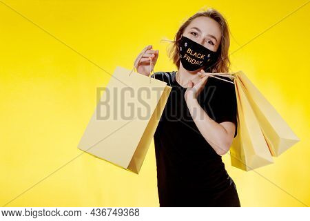 Black Friday Sale. Woman In Face Mask With Black Friday Shopping Bags In Hands. Sale During Pandemic