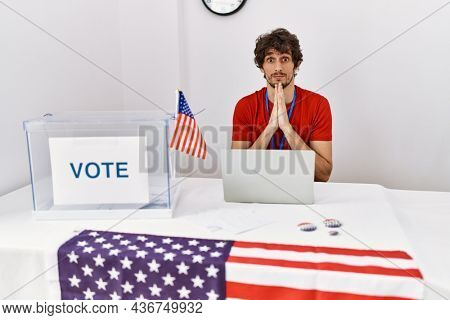 Young hispanic man at political election sitting by ballot praying with hands together asking for forgiveness smiling confident.