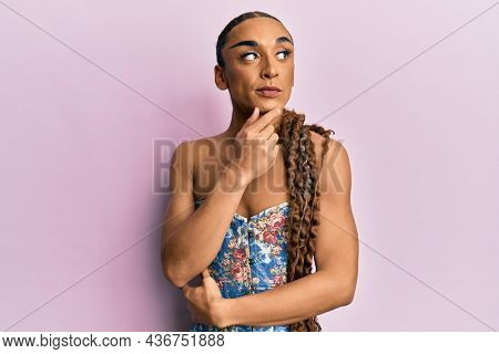 Hispanic man wearing make up and long hair wearing elegant corset with hand on chin thinking about question, pensive expression. smiling with thoughtful face. doubt concept.
