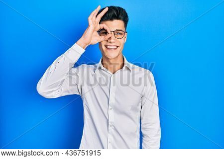 Young hispanic man wearing casual clothes and glasses smiling happy doing ok sign with hand on eye looking through fingers