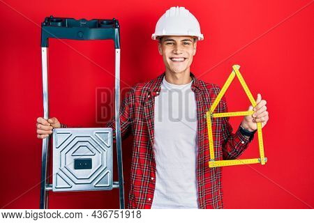 Young hispanic man wearing handyman uniform holding construction stairs and house project smiling with a happy and cool smile on face. showing teeth.
