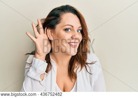 Young caucasian woman wearing casual clothes smiling with hand over ear listening and hearing to rumor or gossip. deafness concept.