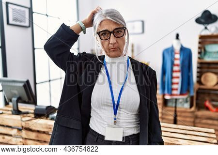Middle age grey-haired woman working as manager at retail boutique confuse and wonder about question. uncertain with doubt, thinking with hand on head. pensive concept.