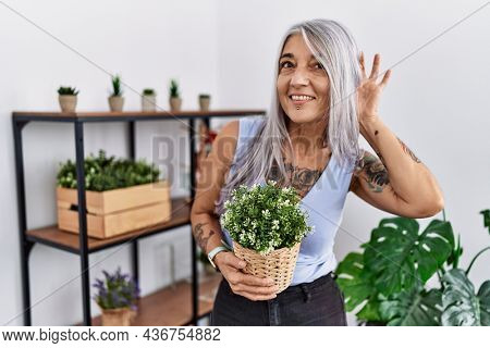 Middle age grey-haired woman holding green plant pot at home smiling with hand over ear listening an hearing to rumor or gossip. deafness concept.