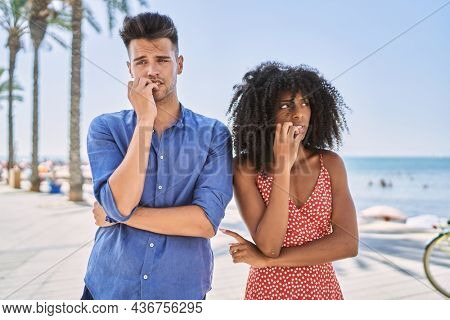 Young interracial couple outdoors on a sunny day looking stressed and nervous with hands on mouth biting nails. anxiety problem.