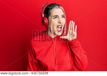 Young modern girl wearing gym clothes and using headphones shouting and screaming loud to side with hand on mouth. communication concept.