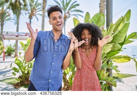 Young interracial couple outdoors on a sunny day celebrating crazy and amazed for success with arms raised and open eyes screaming excited. winner concept