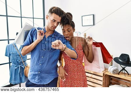 Young interracial couple holding shopping bags at retail shop looking at the watch time worried, afraid of getting late