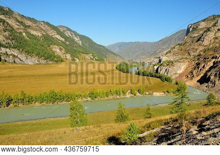 A Winding Bed Of A Beautiful Turquoise River Flowing Serenely Through A Picturesque Valley On A Sunn