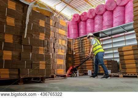 A Male Warehouse Worker Pulling A Pallet Truck. Cardboard Boxes On A Pallet In Warehouse.
