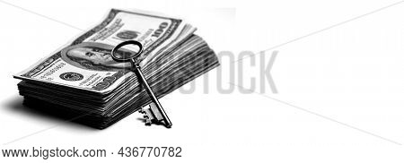 Old key laying on top of stack of cash money