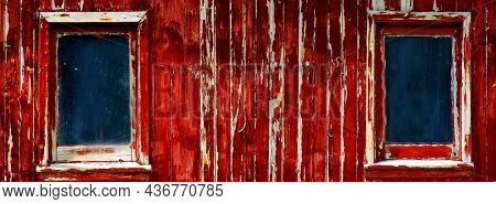 Peeling red paint on weathered old wooden window frames on barn or farm house
